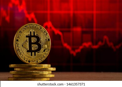 physical bitcoin standing at a wood table in front of a red graph. Bitcoin Bear Market concept