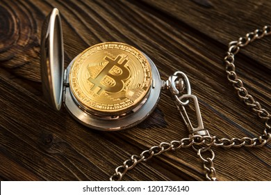 The physical bitcoin and vintage pocket watch shows that time is running out. old-fashioned open clock bokoyunov lying background of a wooden table surface.
