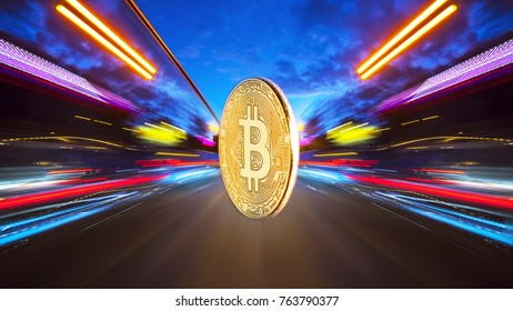 The physical coin is a gold bitcoin on a night road with speed traffic light trails abstract background. Concept Bitcion is speedy money.