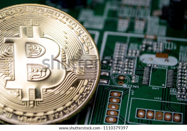 Physical coin representing Bitcoin are aranged on a computer circuit board