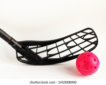 physical education and sport concept. sports games. close up black floorball stick and red ball isolated on white background. copy space for text.