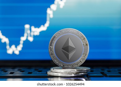 physical ETHEREUM (ETH) cryptocurrency; silver ethereum coin on the background of the chart