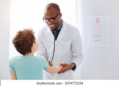 Physical examination. Jolly vigorous male doctor standing while using stethoscope and diagnosing boy