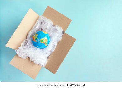 Physical globe, Earth in plastic wrap in carton box on blue background with copy space Recyclable packaging Ecology problem of environmental pollution planet by plastic Earth Day World Environment Day
