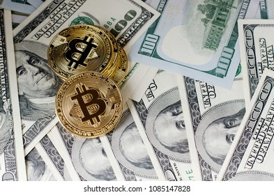 Physical Gold Bitcoin Coin against dollar bills and smartphone on a purple background. Business and financial background