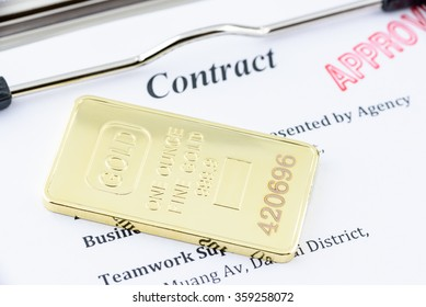 Physical gold bullion with an approved contract on a clipboard.