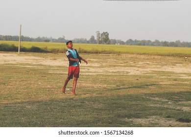 A physical handicapped boy trying to playing gilli danda with his healthy friends on the ground. A disabled boy throwing a object to show he is perfect.