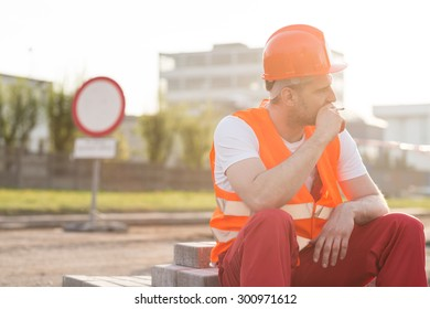 Physical labourer smoking cigarette on construction site