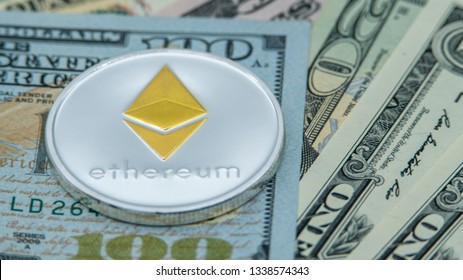 Physical metal silver Ethereum currency over diferents dollars bills United States. Worldwide virtual internet money. USA banknotes. Digital coin cyberspace, cryptocurrency ETH. Online payment