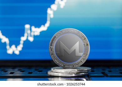 physical MONERO (XMR) cryptocurrency; silver monero coin on the background of the chart