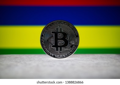Physical silver version of Bitcoin (BTC) and Mauritius Flag on the background. Conceptual image for investors in cryptocurrency and Blockchain Technology.