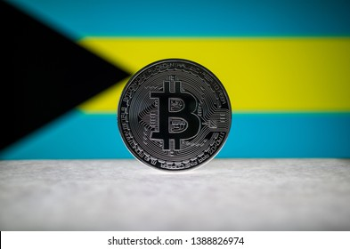 Physical silver version of Bitcoin (BTC) and Bahamas Flag on the background. Conceptual image for investors in cryptocurrency and Blockchain Technology.