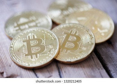 Physical symbol cryptocurrency. Golden bitcoins on a wooden background