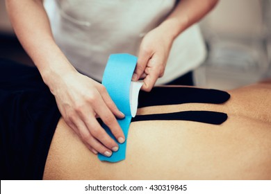 Physical therapist applying kinesio tape onto patient's lower back