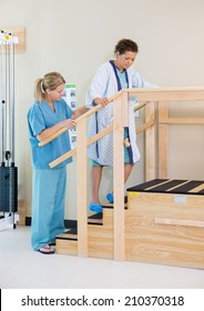 Physical therapist assisting female patient in moving upstairs