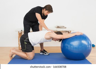 Physical therapist assisting young man with yoga ball in the gym at hospital