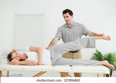 Physical therapist checking the pelvis of a woman in a medical room