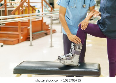 Physical therapist checks the patient's knee in the clinic. Because of pain while wearing orthopedic boot, walking training. medical and orthopedic concept. with copy space for text