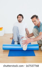 Physical therapist examining young man's leg at the hospital gym