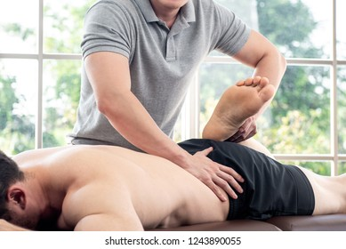 Physical therapist giving massage and stretching to athlete male patient on the bed in clinic, sports medicine concept