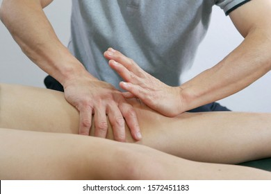 Physical therapist hands treat the knee to the patient on bed