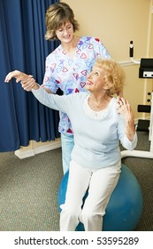 Physical therapist helps senior woman workout on a pilates ball.