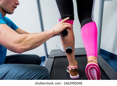 Physical therapist install electrostimulator on the muscles of the legs. Fitness training with an electrostimulator. Physiotherapy.