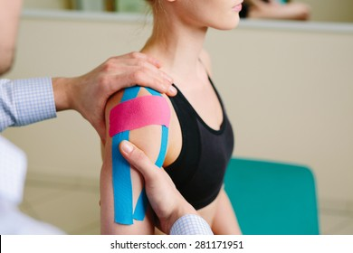 Physical therapist massages injured shoulder with kinesiotaping