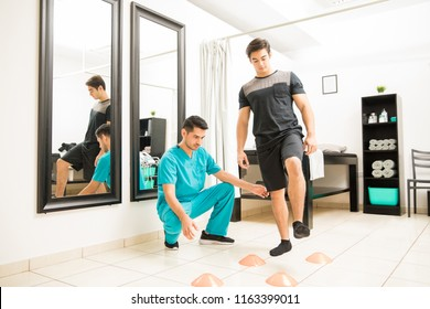 Physical therapist motivating male patient to walk between cones in hospital