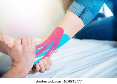 Physical therapist placing kinesio tape on patient's foot
