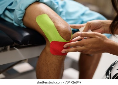 Physical therapist placing kinesio tape on patient's knee.Doctor hand taping for safety athlete muscle and joint.