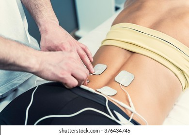 Physical therapist positioning electrodes for lower back muscle treatment