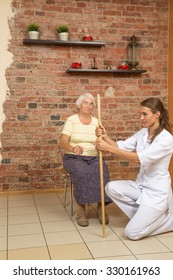Physical Therapist Showing Exercise With A Stick For Senior Woman Sitting On A Chair