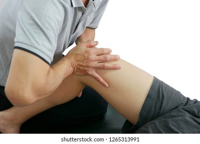 Physical therapist treats the knee to the patient on white background