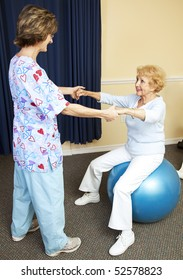 Physical therapist using pilates ball to work with senior chiropractic patient.