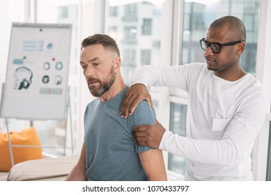 Physical therapy. Smart nice man touching his patients shoulder while doing the therapy