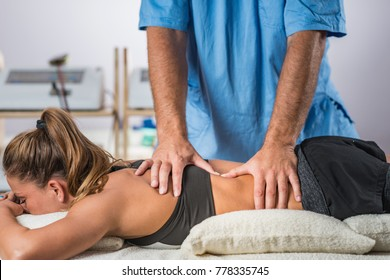 Physical therapy. Therapist addressing lower back muscles