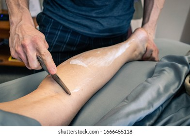 Physical therapy of a woman's calf being scraped for muscle recovery.