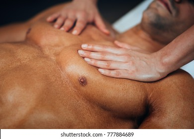Physical therapyst massaging chest of male athelete