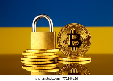 Physical version of Bitcoin, golden padlock and Ukraine Flag. Prohibition of cryptocurrencies, regulations, restrictions or security, protection, privacy.