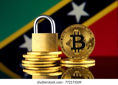 Physical version of Bitcoin, golden padlock and Saint Kitts and Nevis Flag. Prohibition of cryptocurrencies, regulations, restrictions or security, protection, privacy.