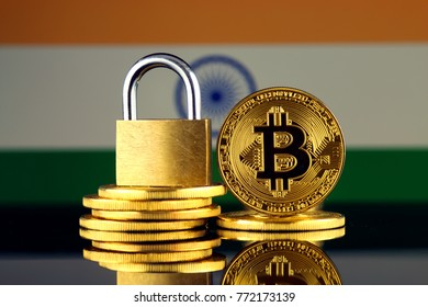 Physical version of Bitcoin, golden padlock and India Flag. Prohibition of cryptocurrencies, regulations, restrictions or security, protection, privacy.