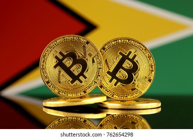 Physical version of Bitcoin and Guyana Flag. Close up.