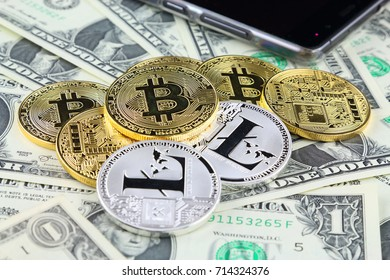 Physical version of Bitcoin and Litecoin (new virtual money) on banknotes of one dollar. Exchange bitcoin cash for a dollar. Conceptual image for worldwide cryptocurrency and digital payment system.