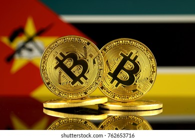 Physical version of Bitcoin and Mozambique Flag. Close up.