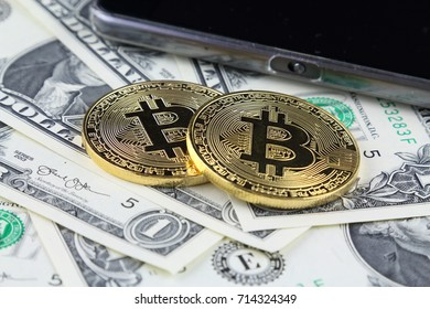 Physical version of Bitcoin (new virtual money) on banknotes of one dollar. Exchange bitcoin cash for a dollar. Conceptual image for worldwide cryptocurrency and digital payment system.