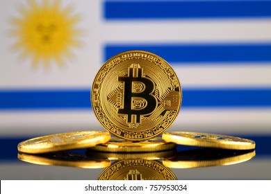 Physical version of Bitcoin (new virtual money) and Uruguay Flag. Conceptual image for investors in cryptocurrency and Blockchain Technology in Uruguay.