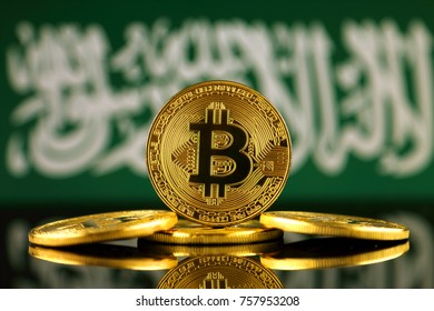 Physical version of Bitcoin (new virtual money) and Saudi Arabia Flag. Conceptual image for investors in cryptocurrency and Blockchain Technology in Saudi Arabia.