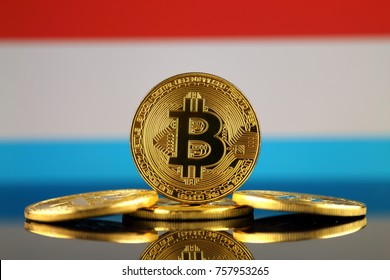 Physical version of Bitcoin (new virtual money) and Luxembourg Flag. Conceptual image for investors in cryptocurrency and Blockchain Technology in Luxembourg.