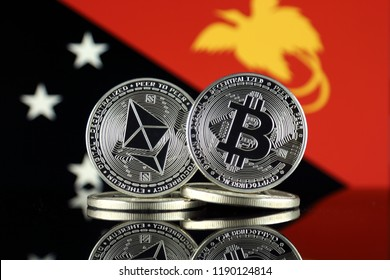 Physical version of Ethereum (ETH), Bitcoin (BTC) and Papua New Guinea Flag. 2 largest cryptocurrencies in terms of market capitalization.